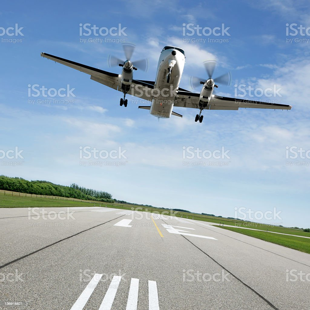 XL propeller airplane landing on runway stock photo