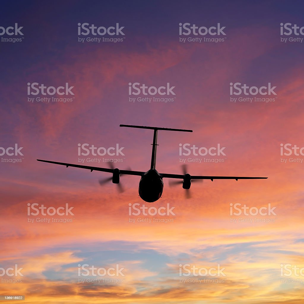 propeller airplane taking off at sunset royalty-free stock photo