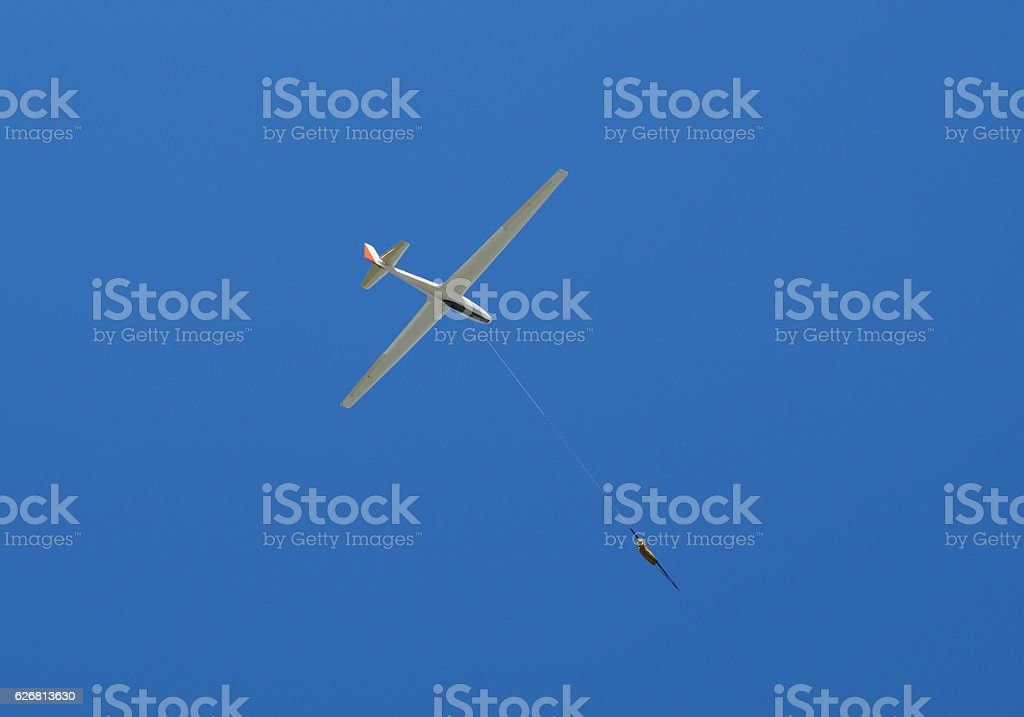 propeller-driven airplane is towing a glider stock photo