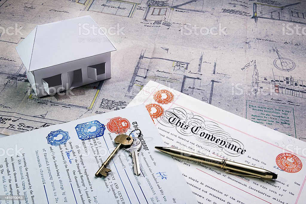 Property and Mortgage deeds sit on top of plans stock photo