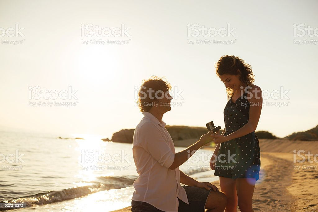Proposing woman at seaside in summer is romantic stock photo