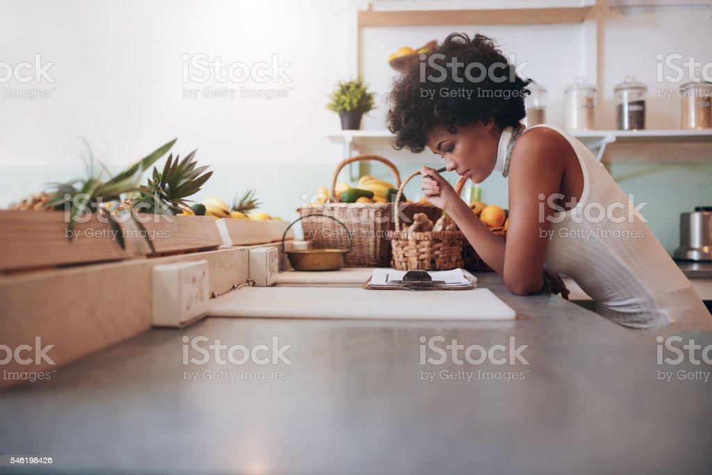 Female proprietor of a juice bar calculating a her business expenses....