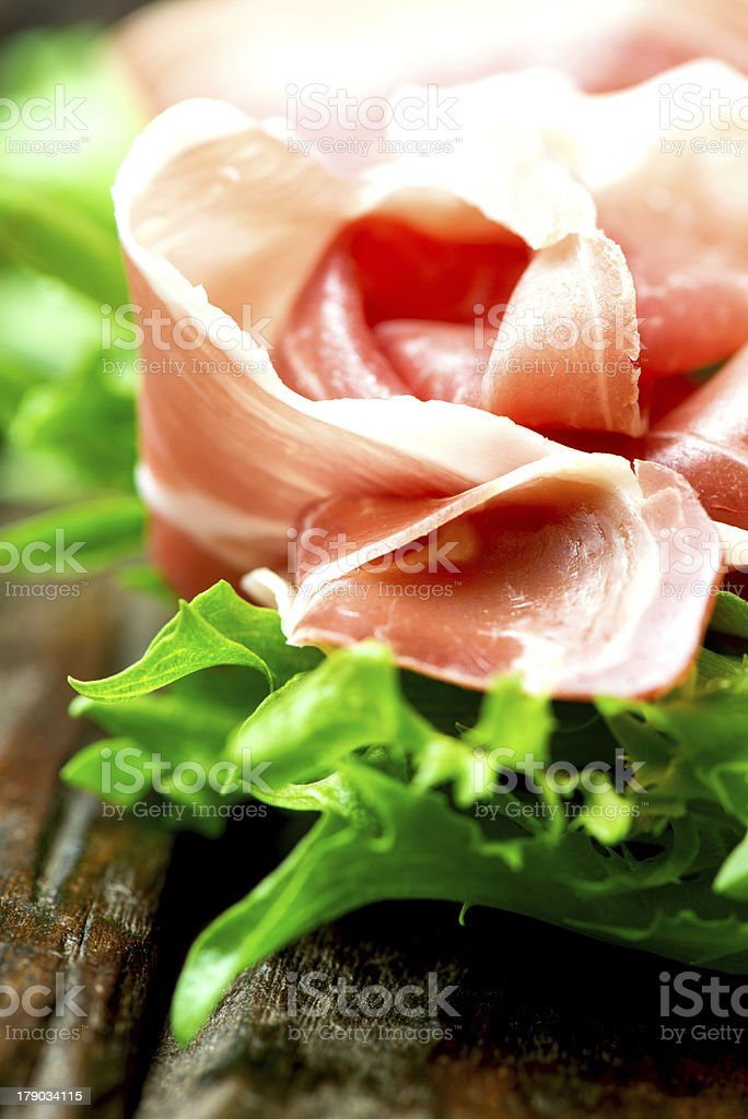 Prosciutto and salad leaves on wooden old table close up royalty-free stock photo