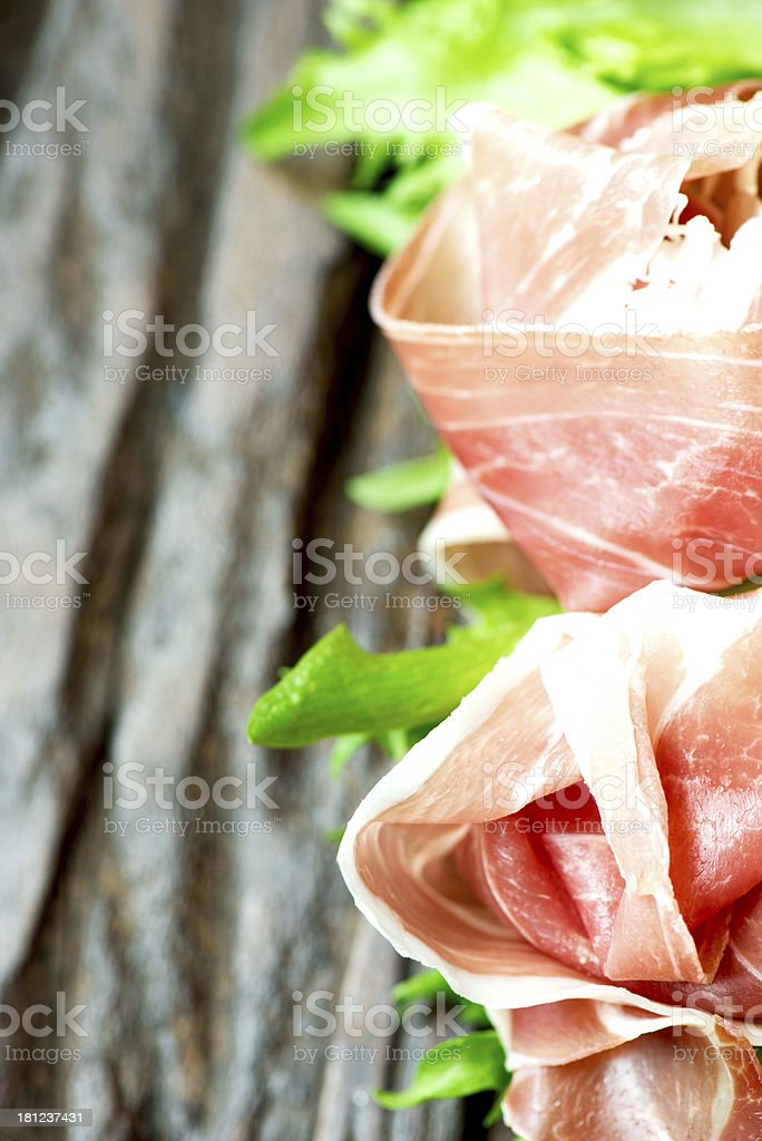 Prosciutto and salad leaves on wooden old table copy space royalty-free stock photo
