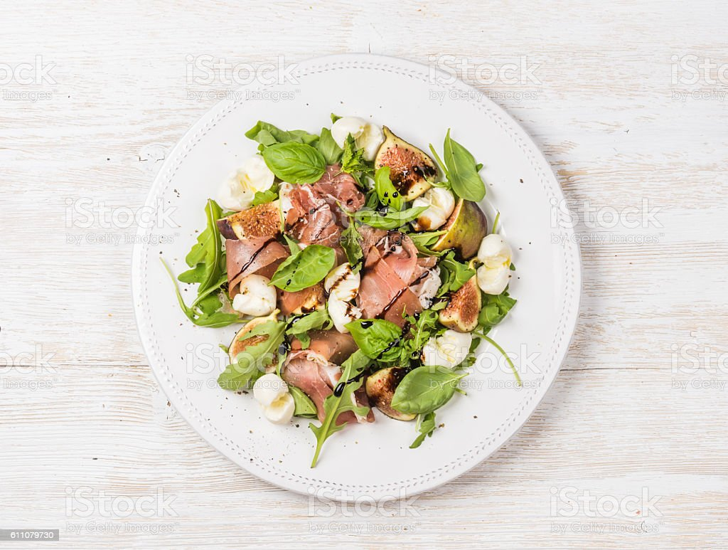 Prosciutto, arugula, basil, figs salad and glass of red wine stock photo
