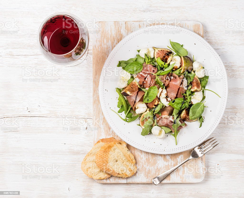 Prosciutto, arugula, figs salad with baguette slices and wine stock photo