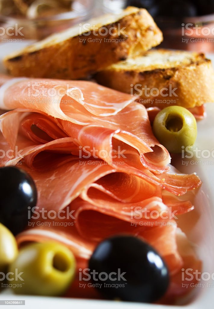 Prosciutto, bread and black and green olives stock photo