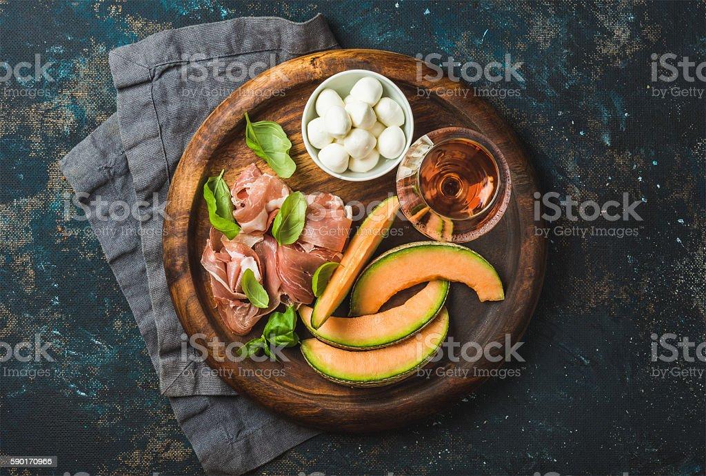 Prosciutto, cantaloupe melon, mozzarella cheese and glass of rose stock photo