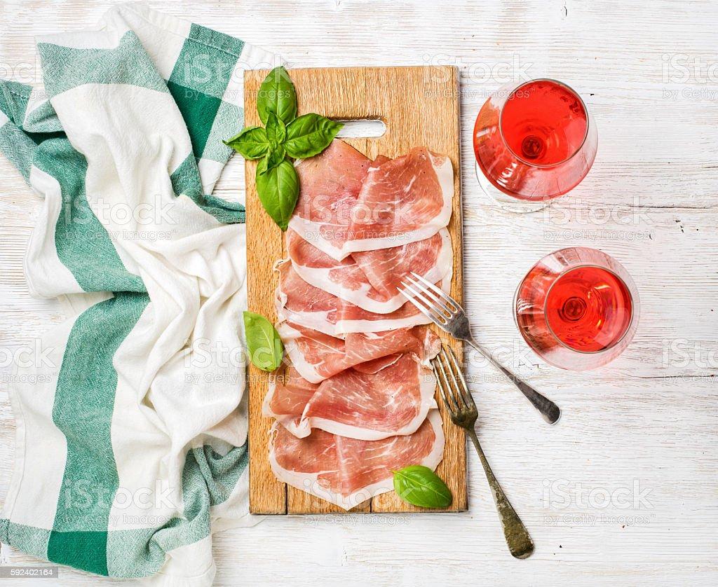 Prosciutto di Parma ham slices and rose wine glasses stock photo
