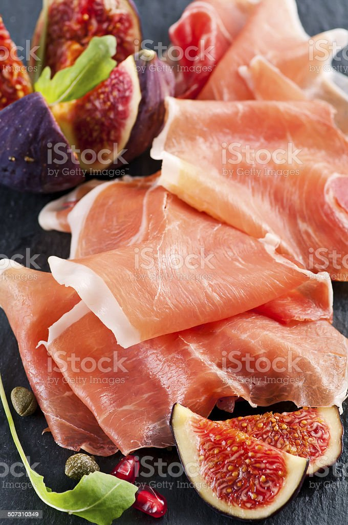 Prosciutto with Fig on a Black Plate stock photo
