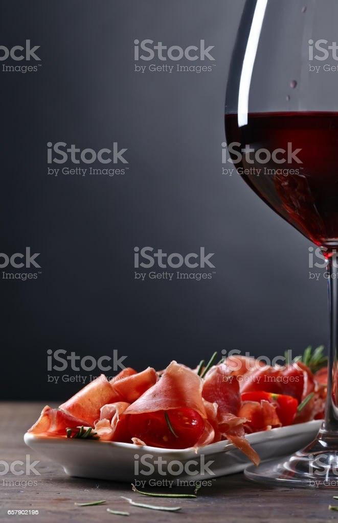 Prosciutto with  rosemary and glass of red wine stock photo