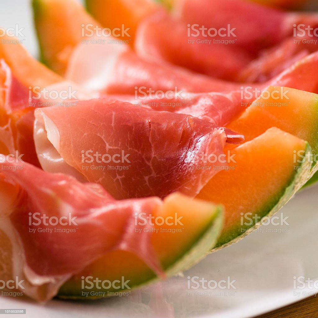 Prosciutto wrapped melon wedges on a white plate stock photo