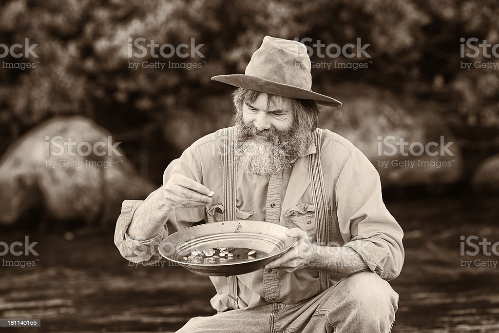 Prospector panning for gold sepia stock photo