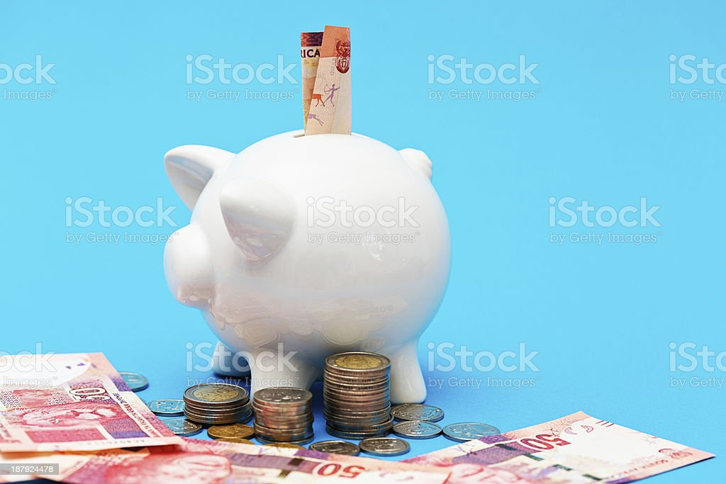 Prosperous piggybank overflowing with South African banknotes and coins royalty-free stock photo