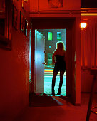 Prostitute Standing in Nightclub Doorway Looking Out