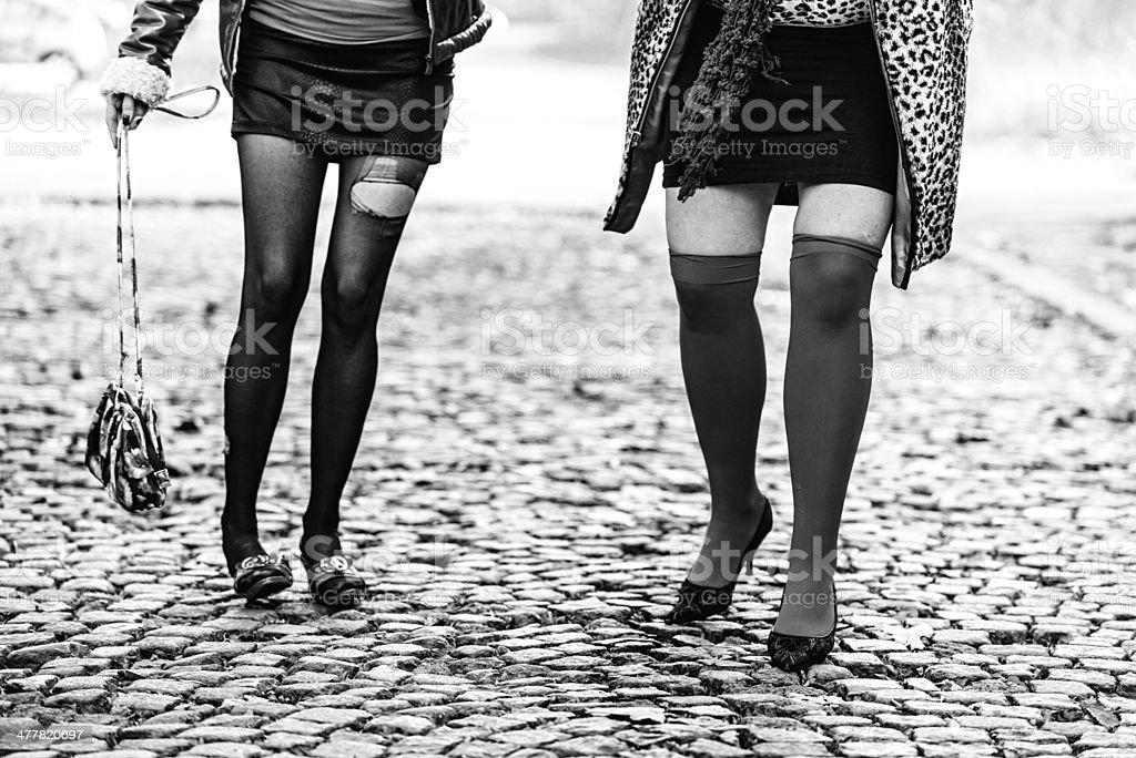 Prostitutes walking on cobblestone street stock photo