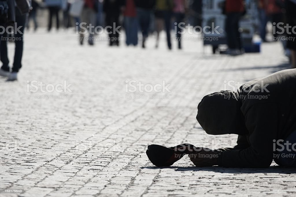 Prostrate homeless man begging for money stock photo