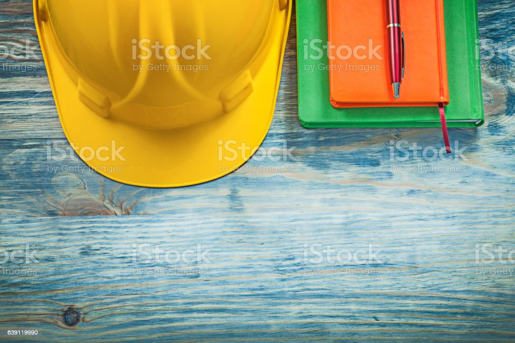 Protective building helmet notepads ballpoint pen on wood board stock photo