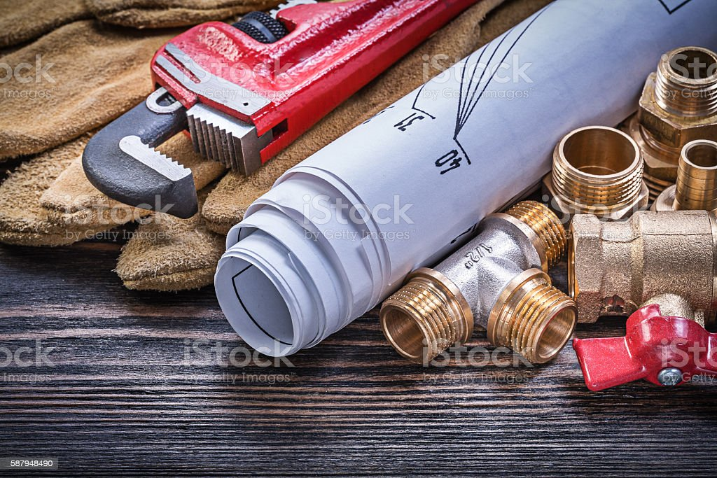 Protective gloves monkey wrench blueprints brass plumbing fittin stock photo