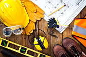 Protective workwear and construction blueprint on wood background
