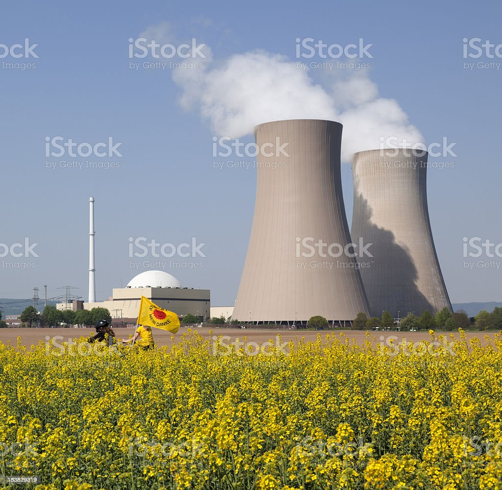 Protest at Nuclear power station with cooling towers behind canola royalty-free stock photo