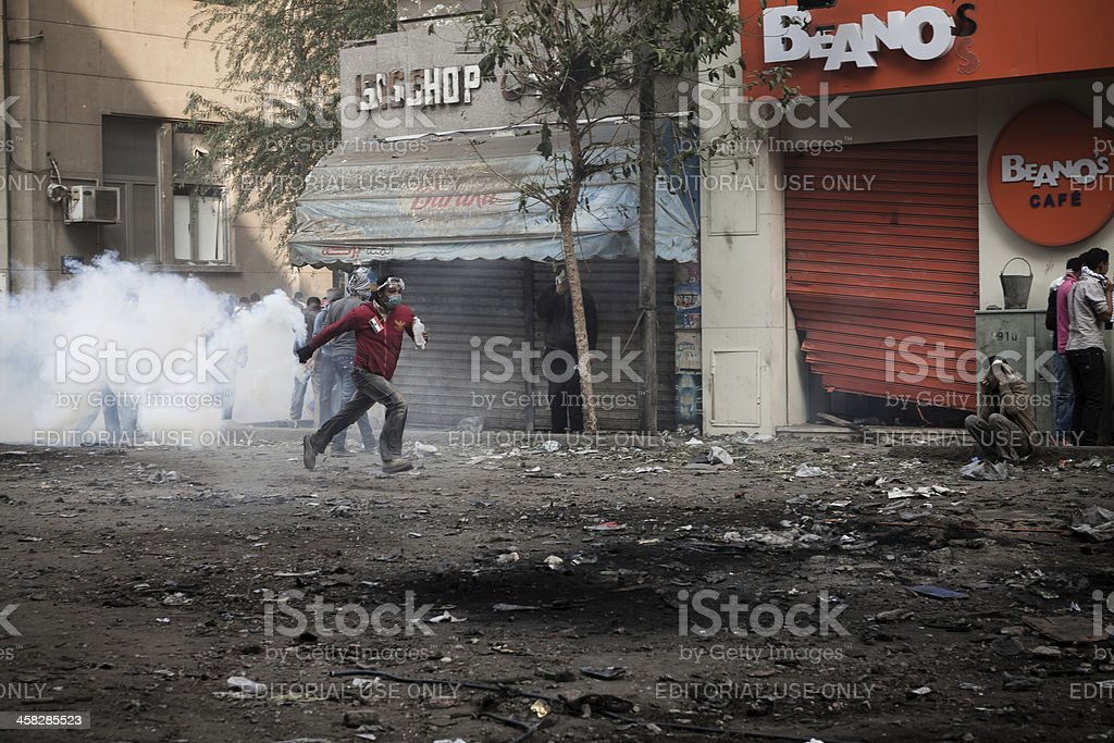 Protester running with tear gas container stock photo