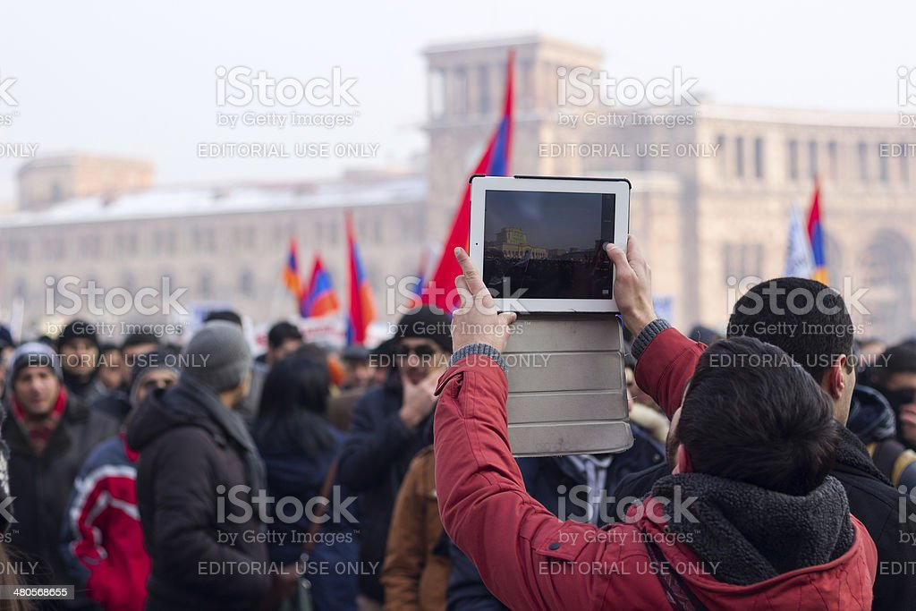 Protester uses a tablet to photograph protest demonstration stock photo