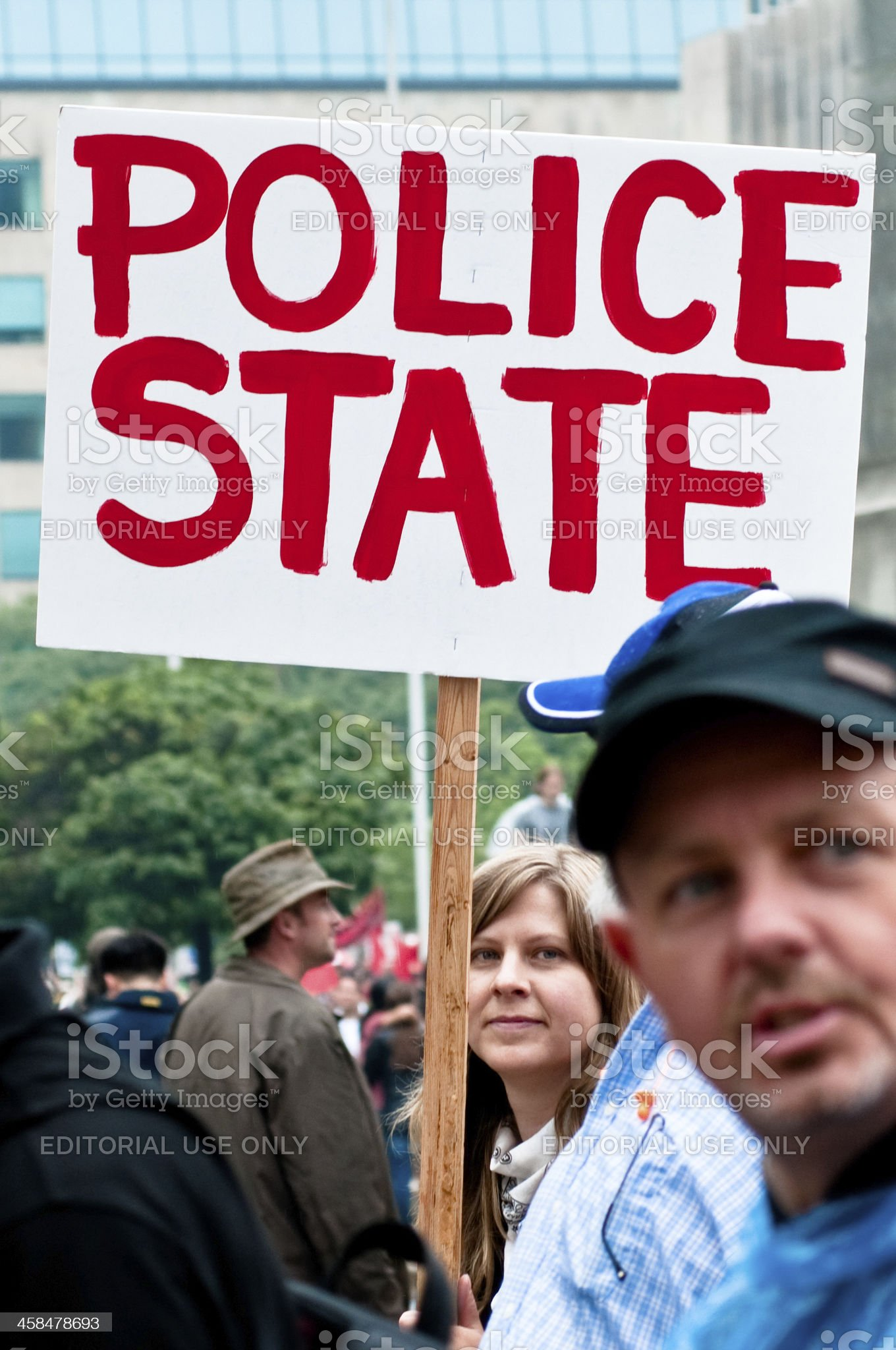 """Protester with a """"Police State"""" sign royalty-free stock photo"""