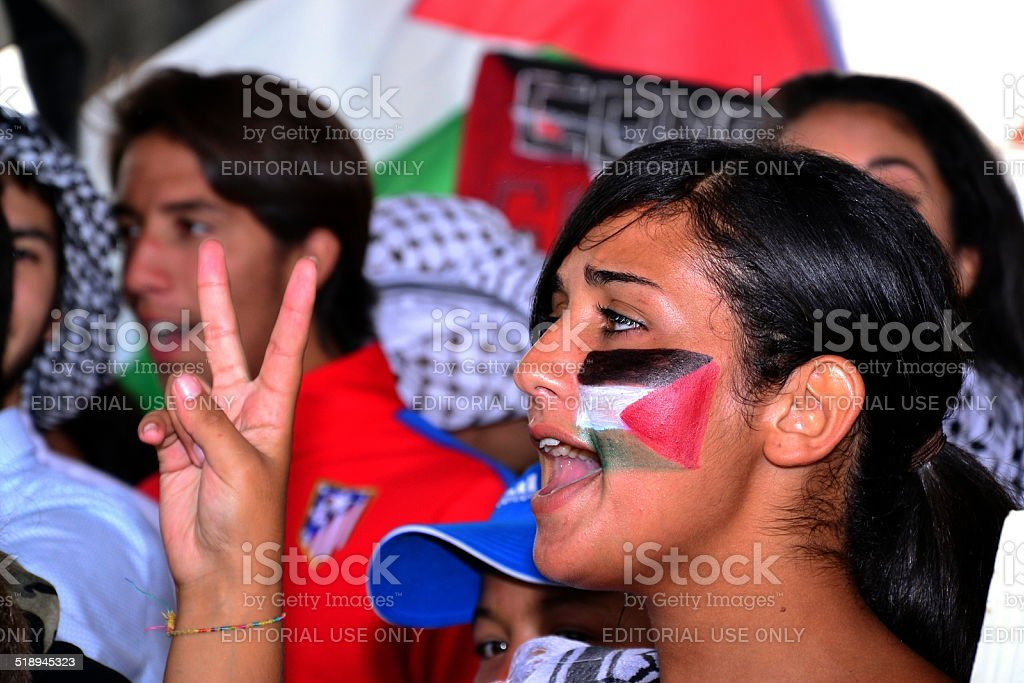 Protesters gather with a Palestinian flag on her cheek stock photo