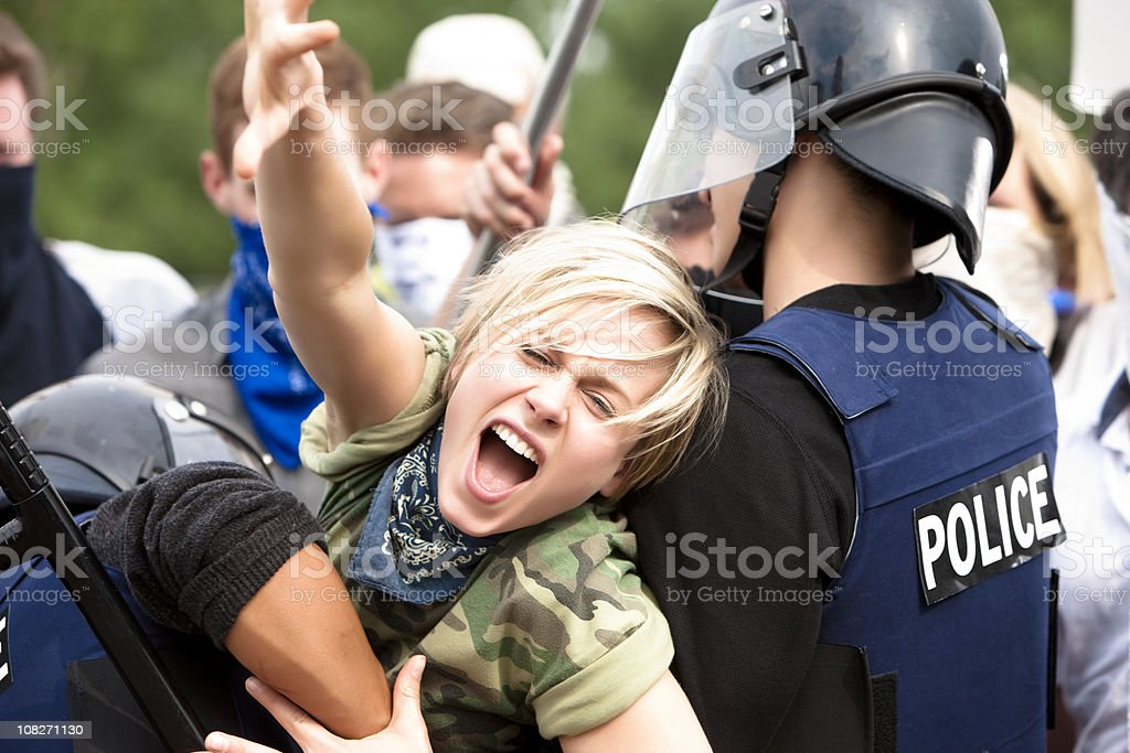 Protestor Trying to Get Through Police Barricade stock photo