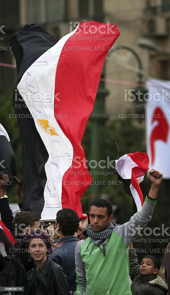 protestors cheering behind egyptian flag stock photo