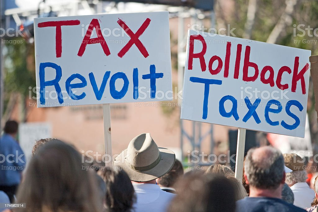 Protestors holding up tax revolt signs stock photo