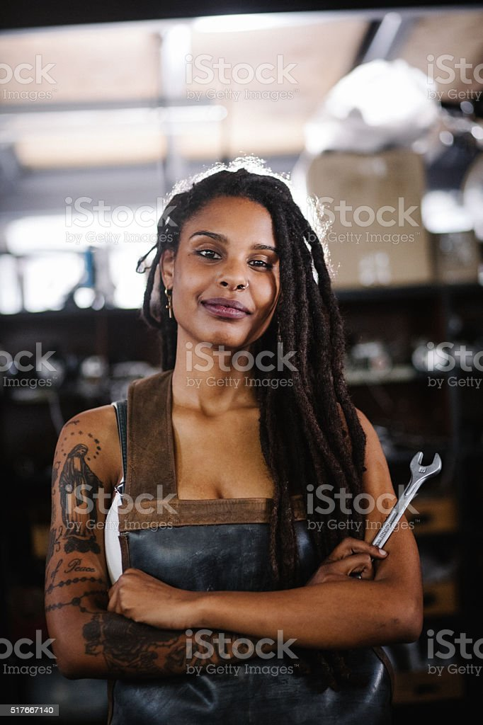 Proud afro craftswoman in her workshop with arms crossed stock photo