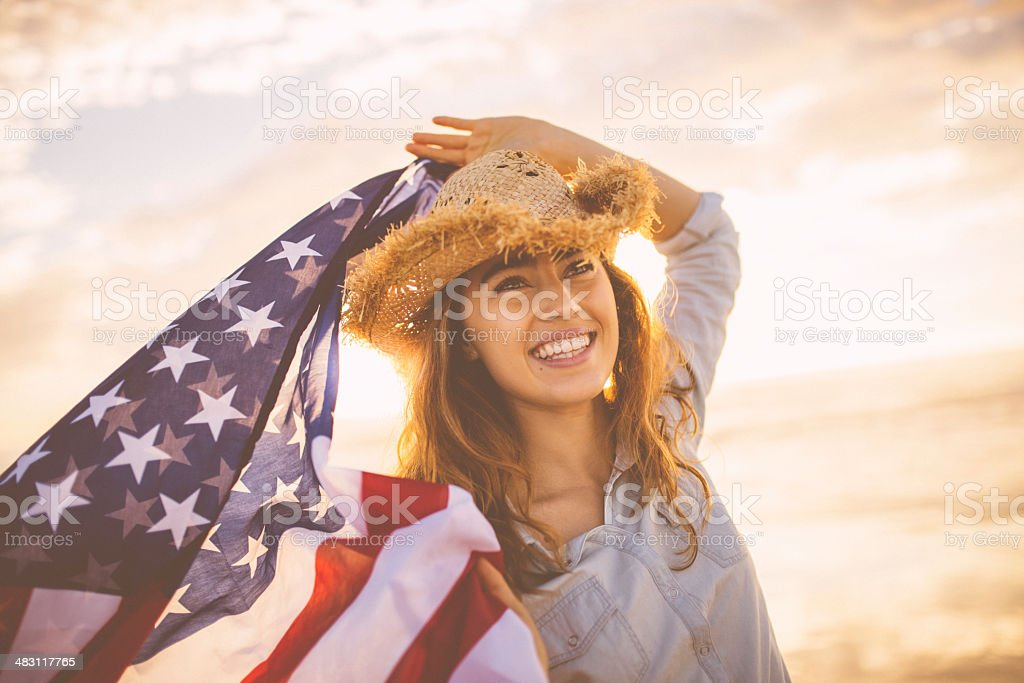 Proud american girl holding stars and stripes stock photo