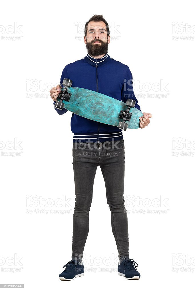 Proud bearded hipster carrying and showing skateboard to camera stock photo