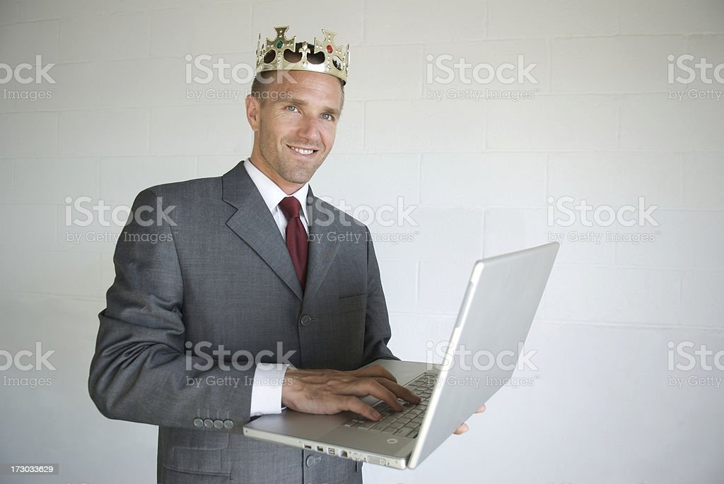 Proud Businessman Wearing Crown Smiling with Laptop stock photo