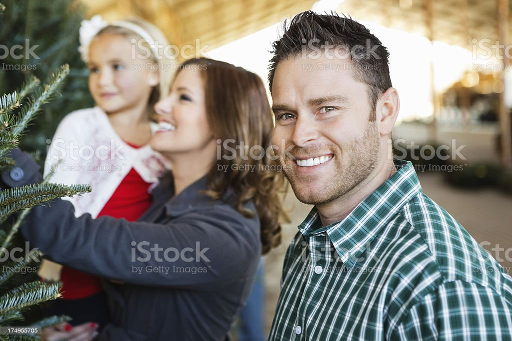 Proud dad selecting Christmas tree with family royalty-free stock photo