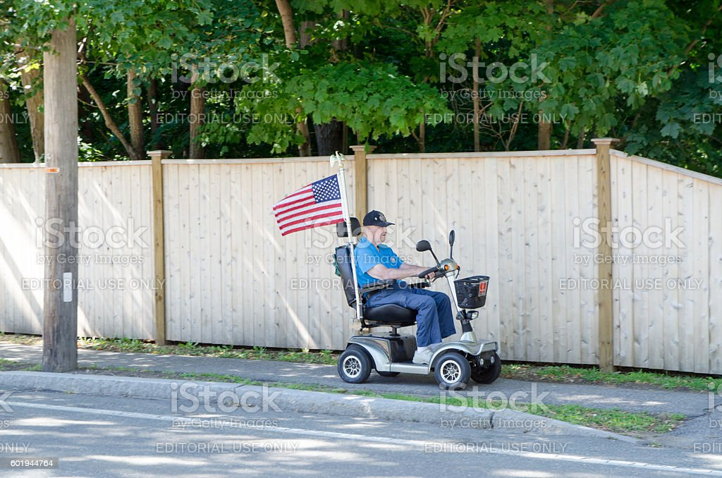 Proud elderly american in a four-wheeled electrical mobility scooter stock photo