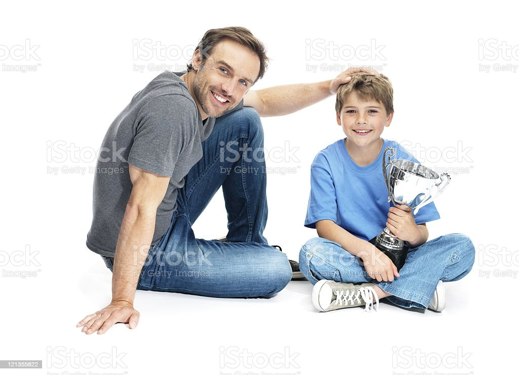 Proud father with his son holding a winning trophy royalty-free stock photo