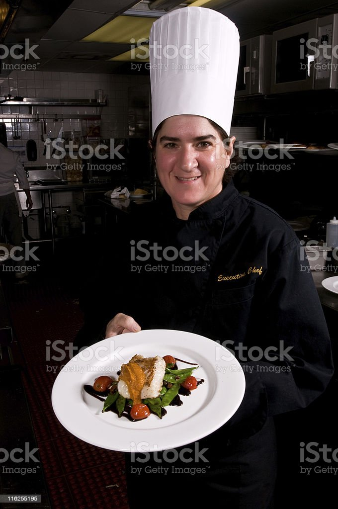 Proud Female chef showing a fish dish royalty-free stock photo