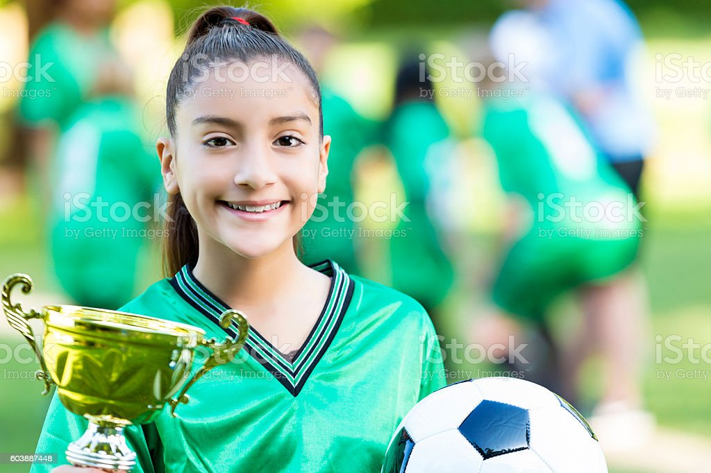 Proud female soccer athlete with championship trophy stock photo