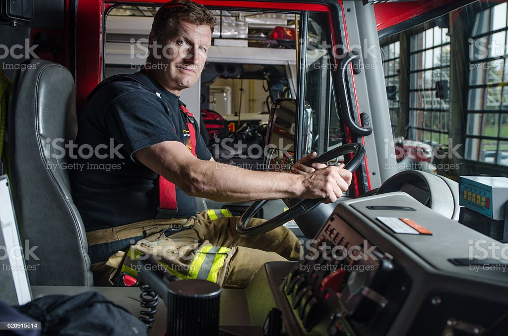 Proud fireman with protection pants sitting behind steering in truck stock photo