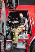 Proud fireman with protection pants sitting in truck