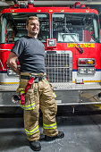 Proud fireman with protection pants standing in front of truck