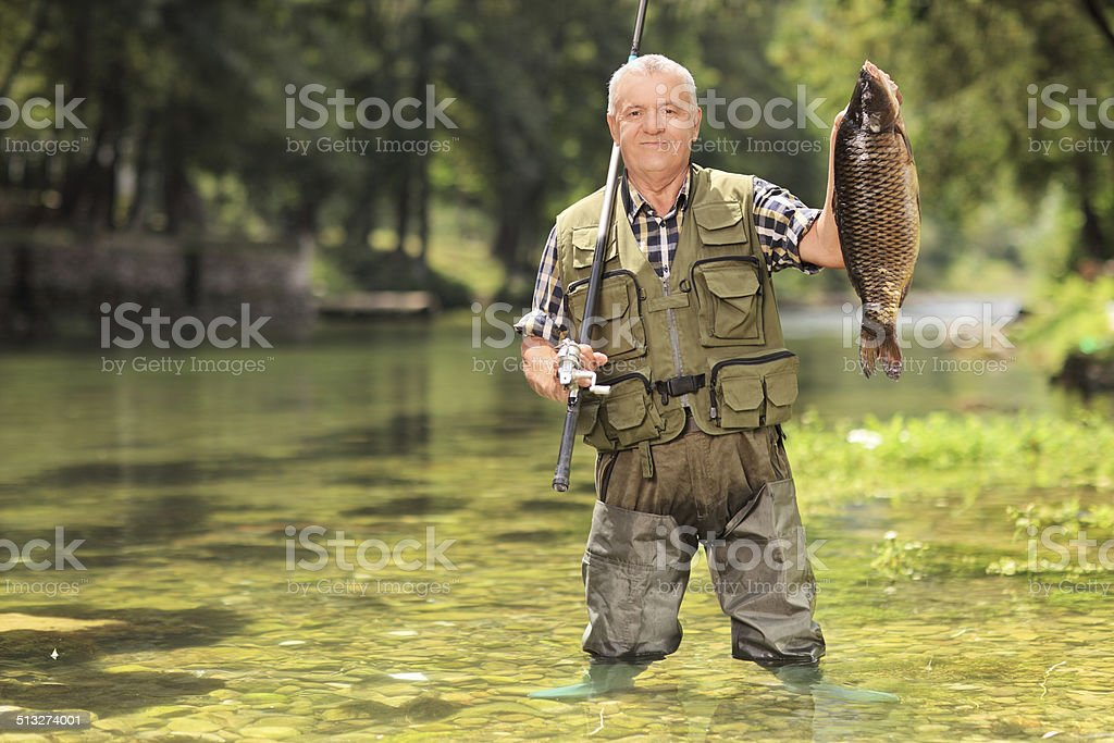 Proud fisherman holding fish in a river stock photo