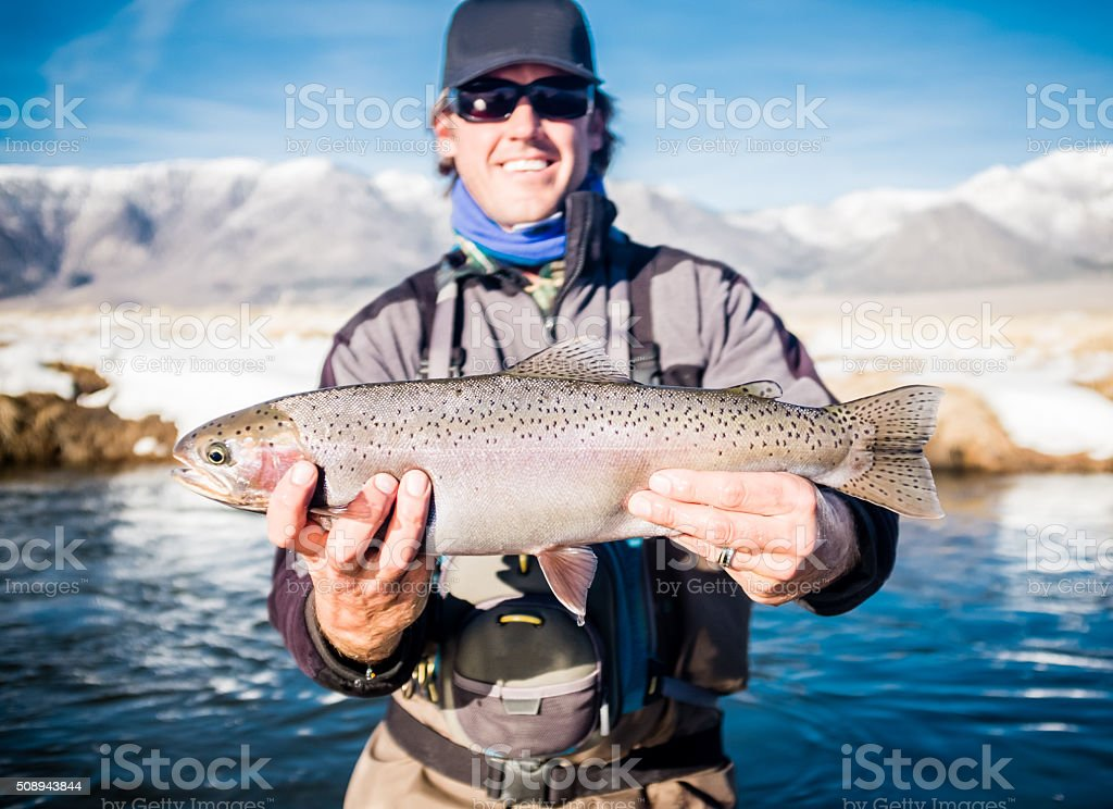 Proud Fisherman Holding Up His Rainbow Trout In Winter stock photo