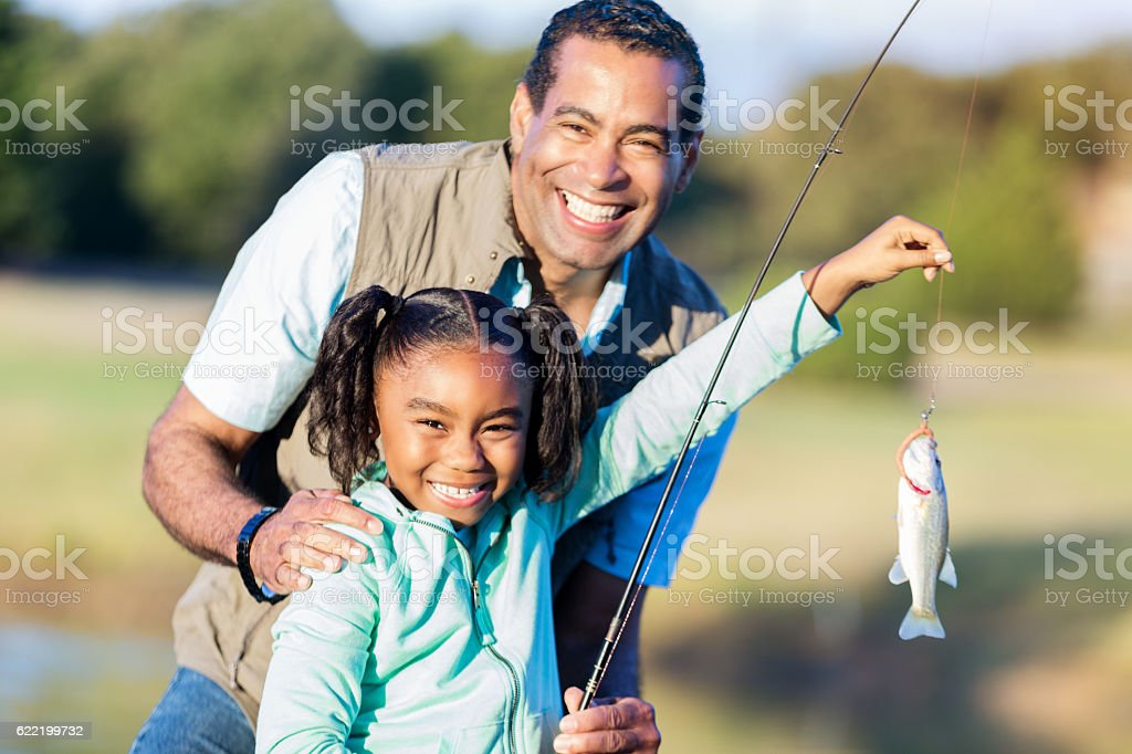Proud girl shows of fish with granddad stock photo