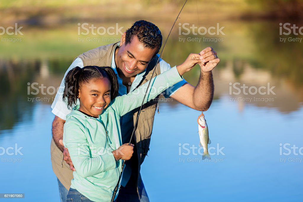 Proud girl shows off fish while fishing with granddad stock photo