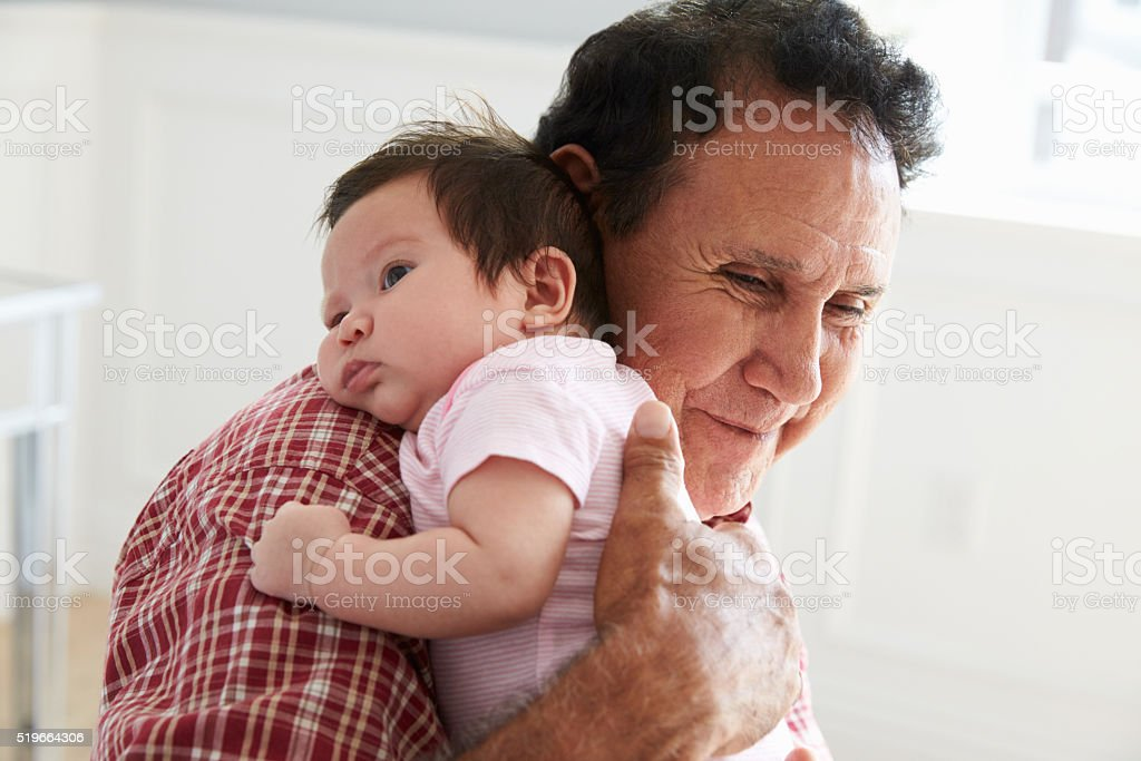 Proud Grandfather Holding Baby Granddaughter stock photo