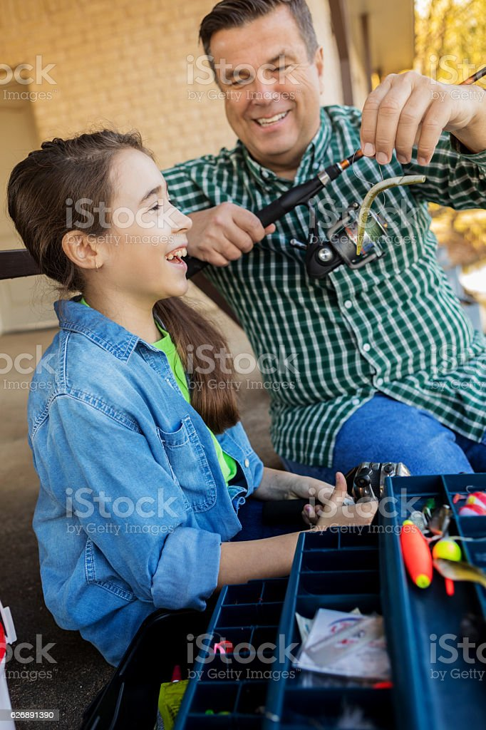 Proud grandpa teaches his granddaughter to fish stock photo